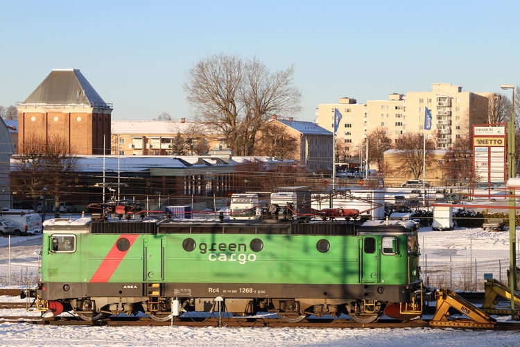 Train on railroad track in city against sky