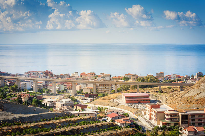 Panoramic view of townscape by sea against sky