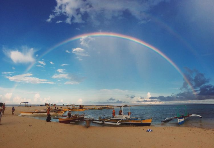 Group of people with boats moored on sea against sky with rainbow