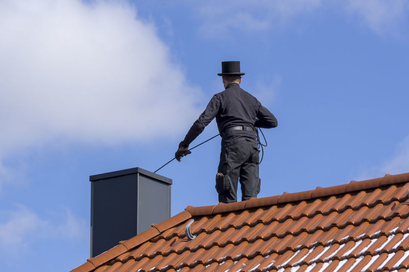 Chimney sweep cleaning a chimney standing on the house roof, lowering equipment down the flue Chimney Cleaning Cloudy Sky Blue Sky House Roof Outdoors Roof Tiled Roof
