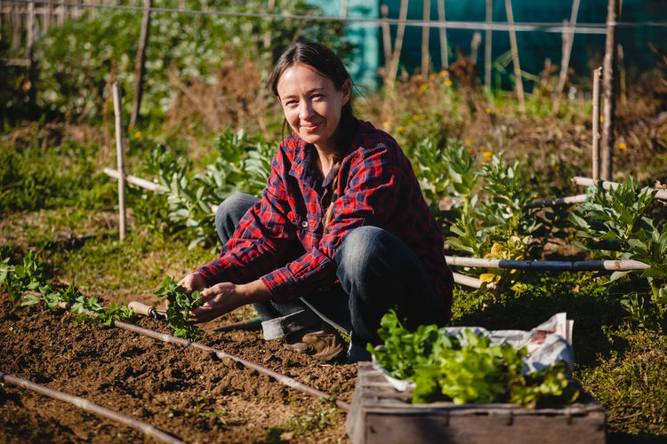 Portrait of smiling young woman with plants in farm