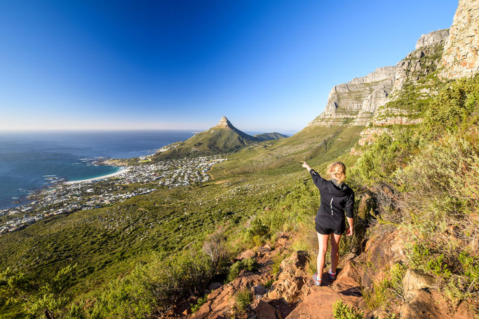 Young female hiker pointing at the suburb of Camps Bay and Lion's Head and Table mountain (right) in Cape Town, South Africa. Seen from Kasteelspoort Hiking Trail, part of Table Mountain National Park. Camps Bay Cape Town Lion's Head South Africa Table Mountain Woman Adventure Africa Beauty In Nature Day Hiker Hiking Leisure Activity Lifestyles Mountain Nature One Person Outdoors Real People Rear View Standing Table Mountain National Park Tourism Woman Hiking Young Woman