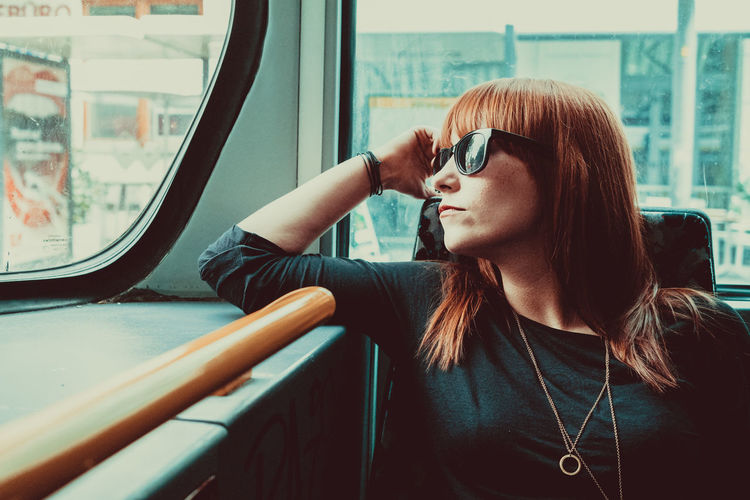 Woman looking through window while sitting in train