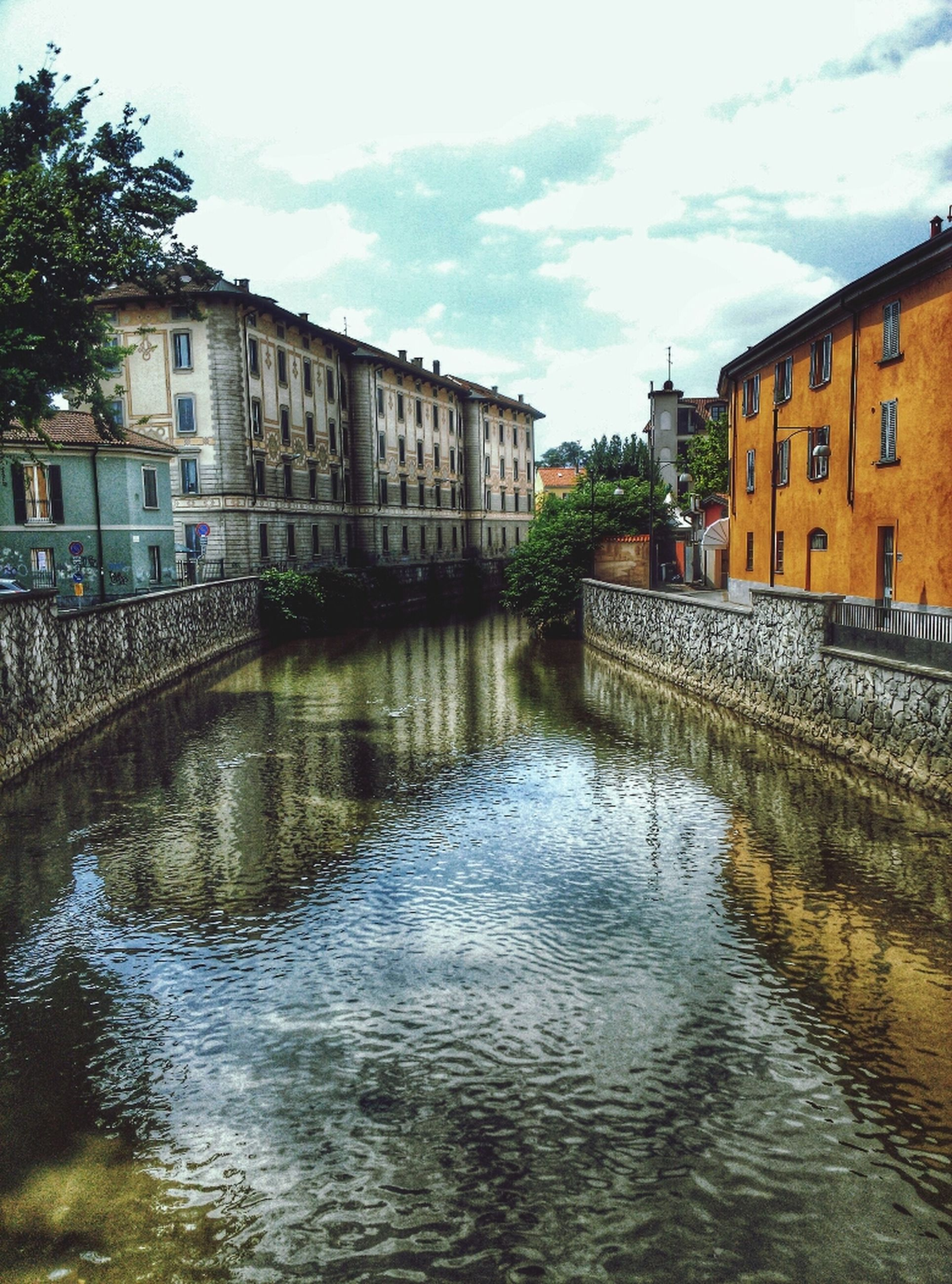 architecture, built structure, building exterior, water, canal, waterfront, sky, reflection, river, house, residential building, residential structure, tree, building, rippled, connection, day, outdoors, cloud - sky, city