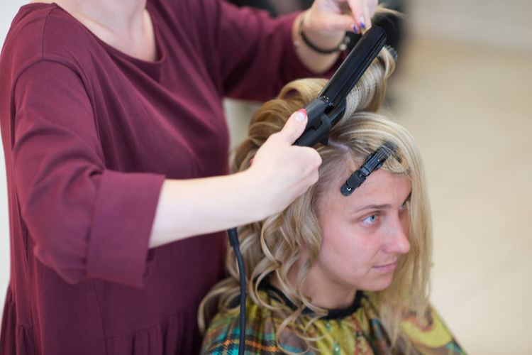 Midsection of female hairdresser using equipment on blond bride at salon