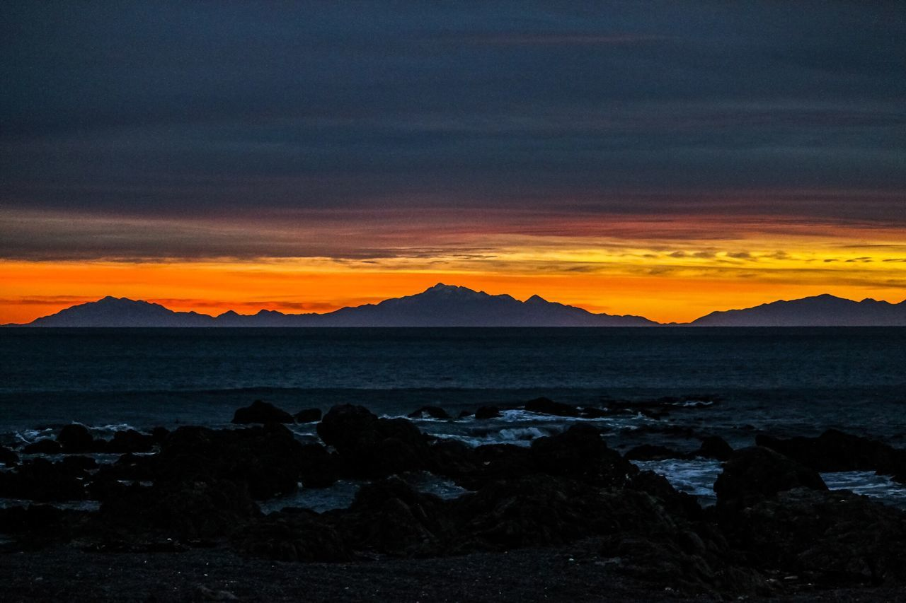 sunset, nature, beauty in nature, scenics, tranquility, tranquil scene, orange color, sky, sea, water, silhouette, outdoors, idyllic, no people, rock - object, horizon over water, beach, landscape, mountain, day