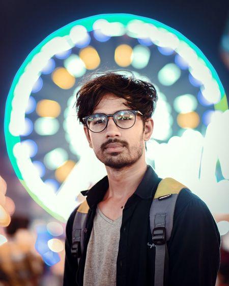 Portrait Of Confident Young Man At Illuminated Amusement Park