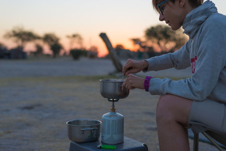 Side View Of Woman Making Tea On Burner At Dusk