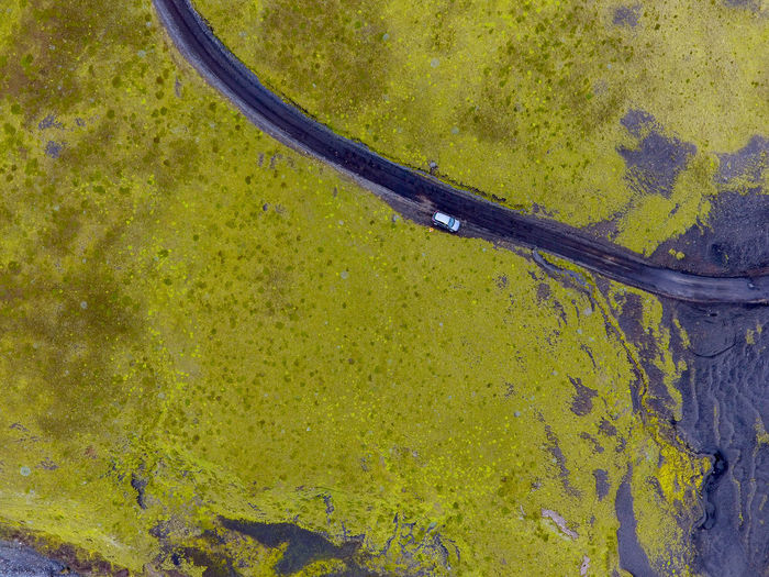Aerial view of car on road amidst green landscape