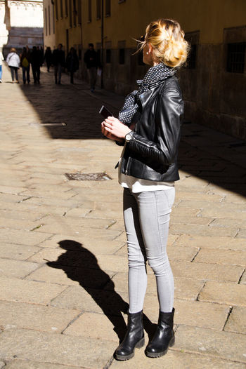 Side view of young woman standing on paved footpath in city