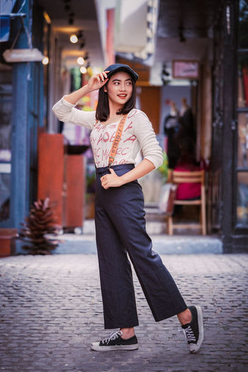 Hey there, let's go this way! www.davidsalaphoto.com www.500p www.instagram.com/momentsb4autumn Peace Architecture Beautiful Woman Building Exterior Built Structure Casual Clothing Day Focus On Foreground Front View Full Length Happiness Holding Leisure Activity Lifestyles One Person Outdoors People Portrait Real People Simple Photography Smiling Standing Travel Destinations Young Adult Young Women