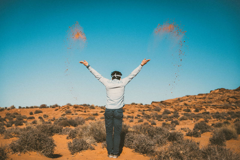 Rear view of man throwing sand while standing at desert against sky