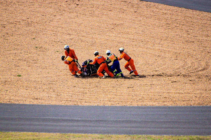 People pushing breakdown motorcycle on field