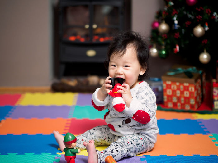 Portrait of cute baby girl playing with toy at home during christmas