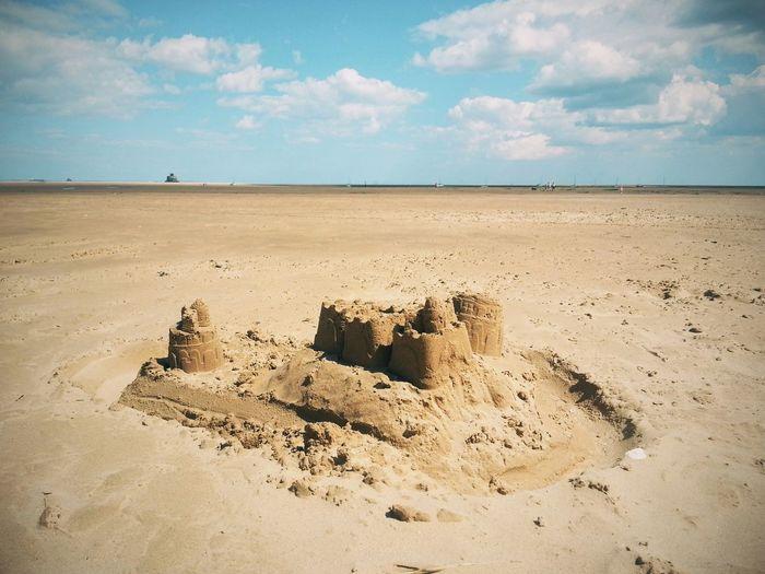 Sandcastle on beach against sky