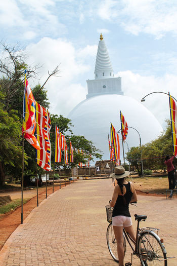 Young woman is standing with a bicycle in front of the temple in Anuradhapura, Sri Lanka Anuradhapura Sri Lanka Travel Architecture Bicycle Building Exterior Built Structure Cloud - Sky Day Flag Men Outdoors Patriotism Place Of Worship Real People Religion Sky Spirituality Temple Tree