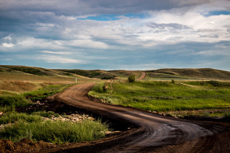 Dirt road on landscape against cloudy sky