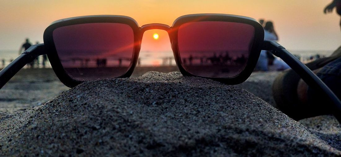 Close-up of sunglasses on rock at beach against sky