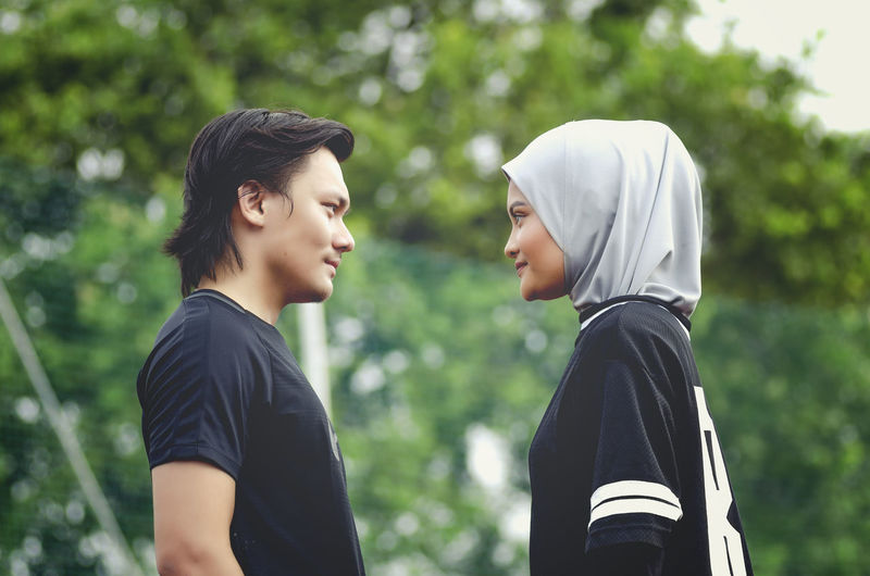 Side view of young couple standing against trees