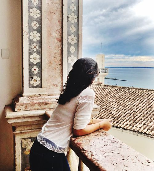 Side view of woman looking at sea while leaning on railing against sky