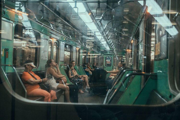 Travel Travel Photography Commuter Crowd Glass - Material Group Of People Illuminated Mode Of Transportation Outdoors Passenger Public Transportation Rail Transportation Real People Seat Sitting Subway Train Train Train - Vehicle Transportation Travel Vehicle Interior Vehicle Seat Window Women