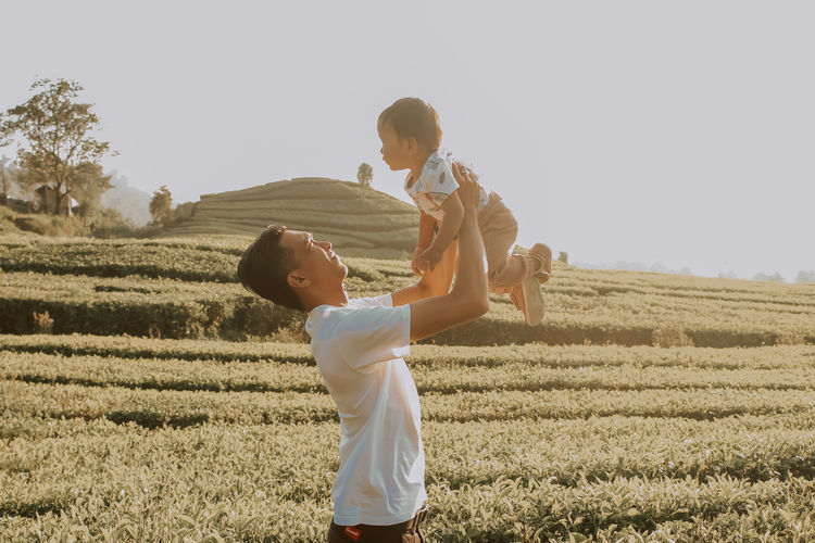 Father Holding Baby On Field Against Sky
