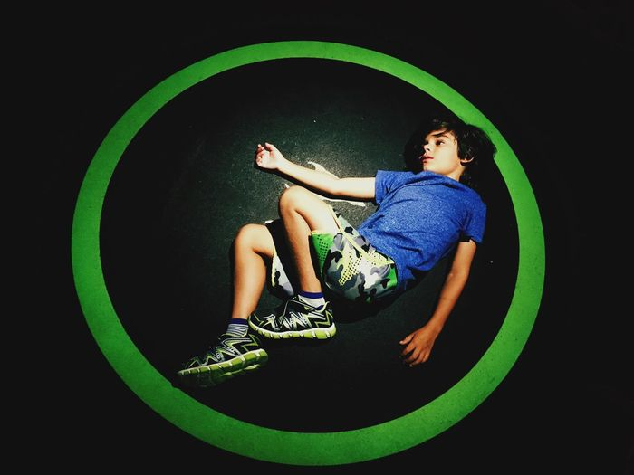 Boy in a circle. Every place we go to, he lays down. One Person Real People Lifestyles Full Length Green Color Indoors  The Creative - 2018 EyeEm Awards Child High Angle View Sitting Standing Women Young Women Childhood Casual Clothing Leisure Activity Females Black Background Lying Down Girls Humanity Meets Technology
