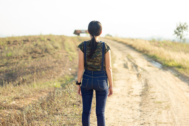 woman, dungarees, background, attractive, beautiful, cheerful, blue, people, female, person, summer, caucasian, looking, casual, clothing, vibrant, posing, long, striped, travel Adult Day Dirt Road Grass Landscape Males  Nature One Man Only One Person Only Men Outdoors People Rear View Sky