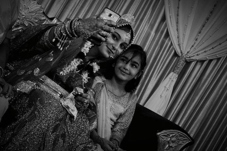 Bride taking selfie with girl at wedding