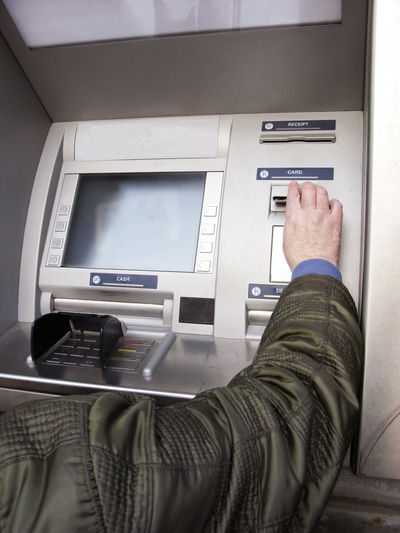 Cropped Image Of Man Using Atm