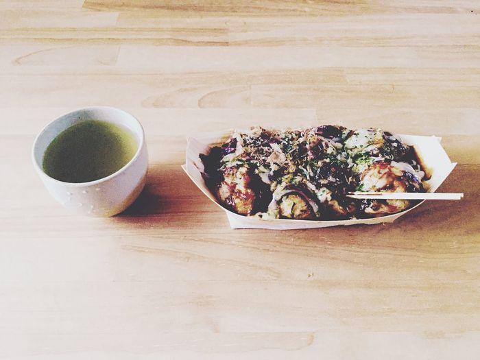 High Angle View Of Green Tea And Takoyaki On Table
