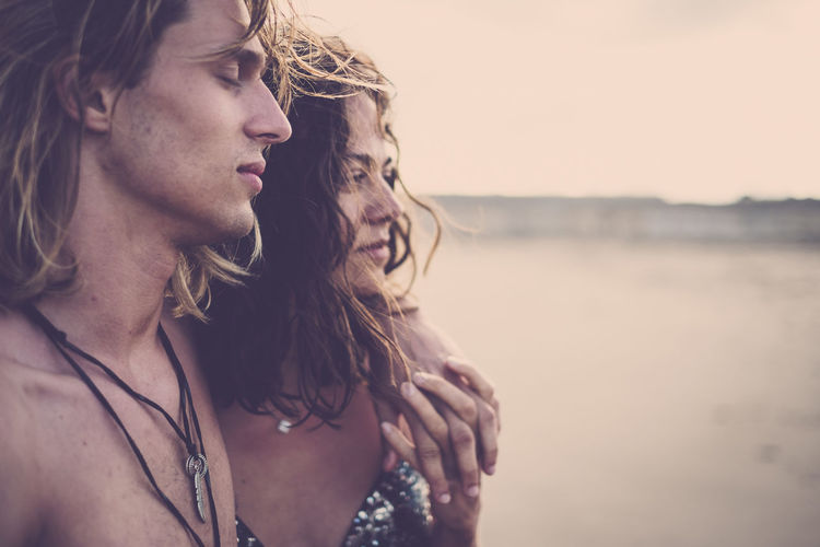 Close-up of young couple standing at beach