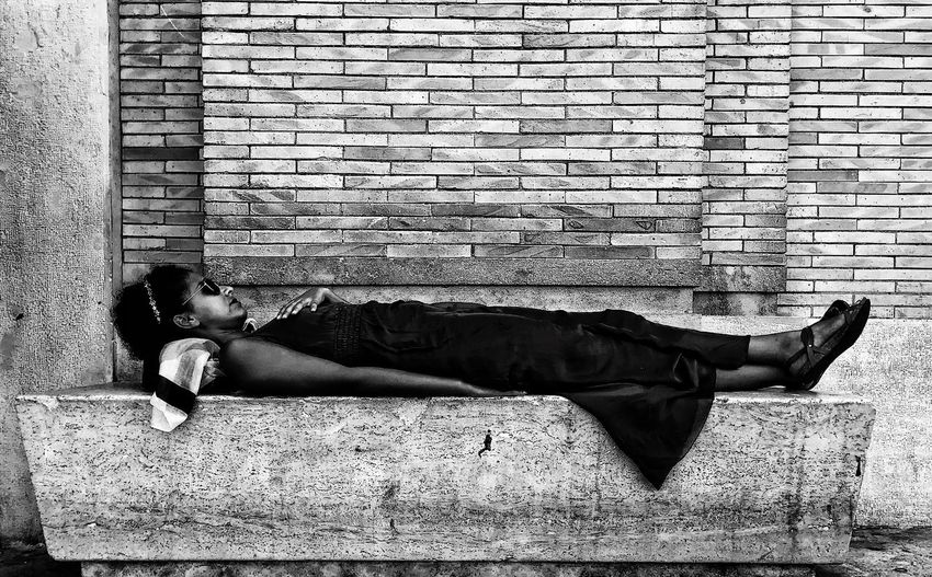 Side view of man sleeping on wall
