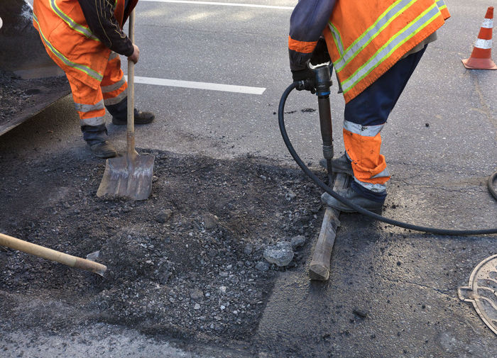 Low section of men working standing on road