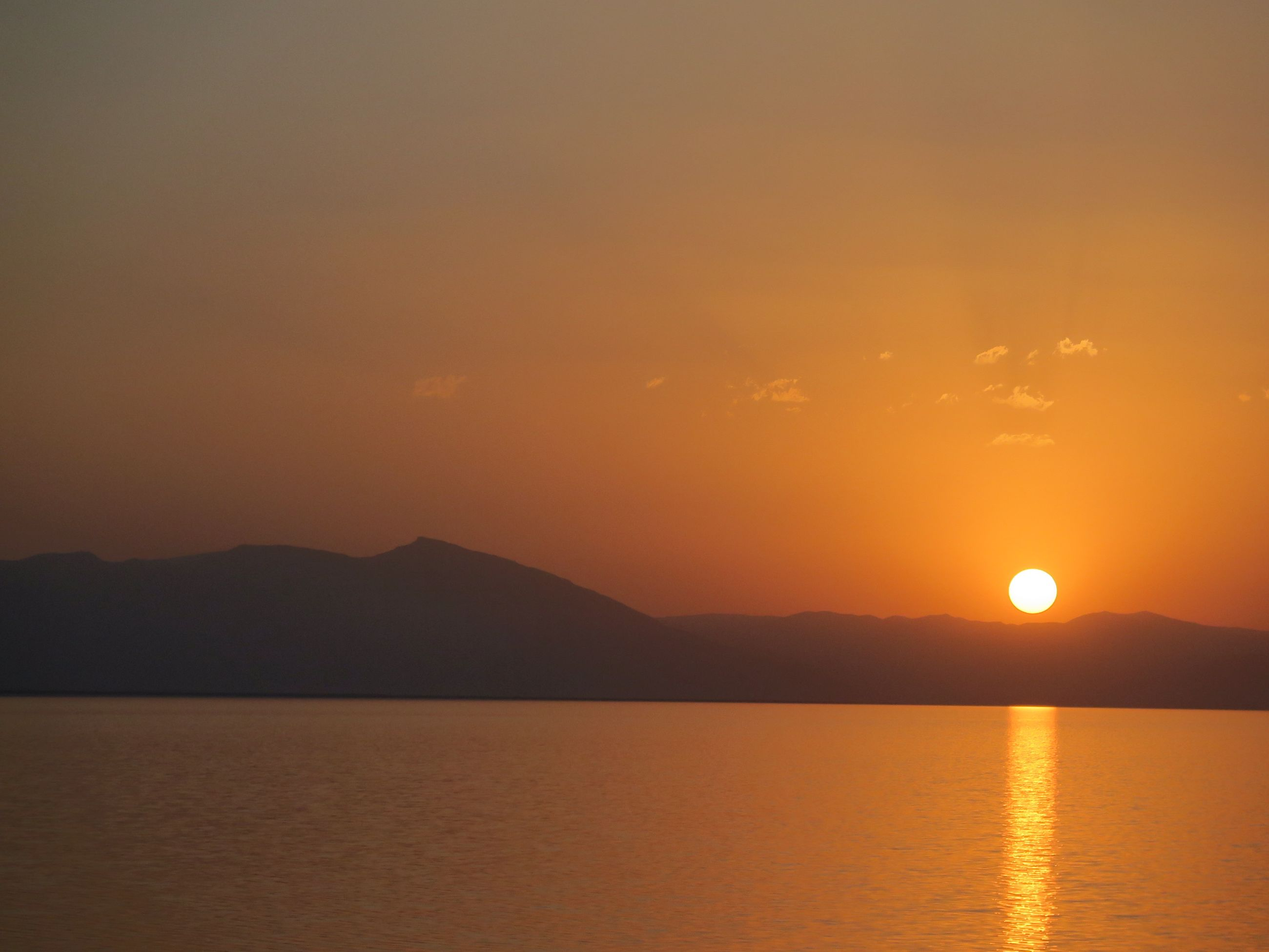 sunset, orange color, scenics, mountain, tranquility, tranquil scene, sun, nature, beauty in nature, silhouette, water, sky, no people, idyllic, reflection, waterfront, sea, mountain range, outdoors, landscape