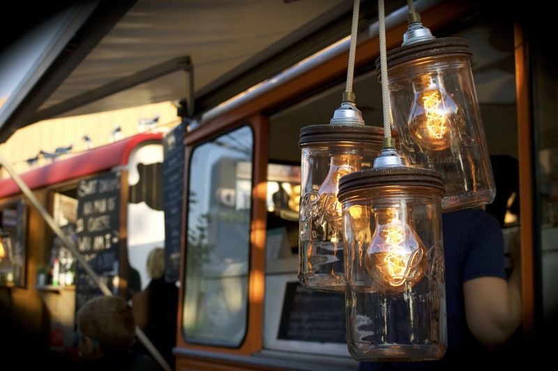 Light bulbs in glass containers hanging outside food truck