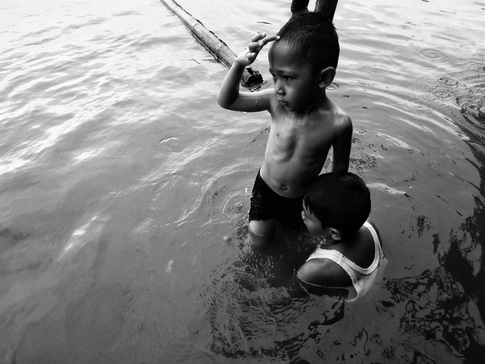 High angle view of shirtless boy standing in lake