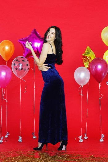 Full length of a smiling young woman with balloons