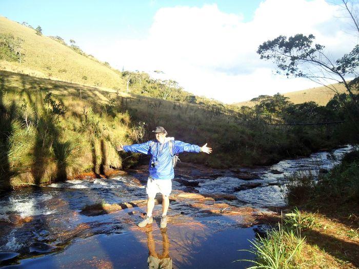 Full length of man jumping in water against sky