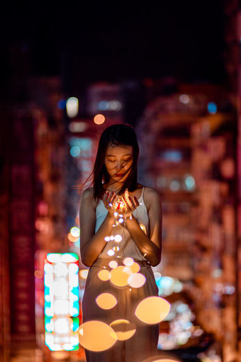Young woman in illuminated string light