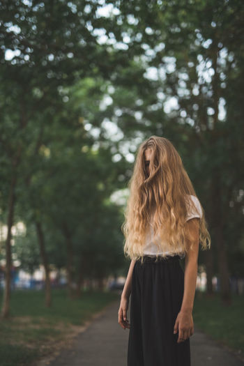 Girl with tousled hair standing against trees
