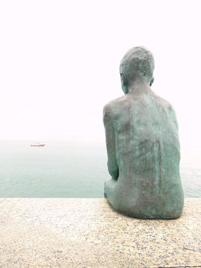 grey day Back Art And Craft Clear Sky Creativity Day Horizon Horizon Over Water Human Representation Land Looking At View Nature No People Outdoors Rear View Representation Scenics - Nature Sculpture Sea Ship At Horizon Shipping  Sky Statue Tranquil Scene Tranquility Water