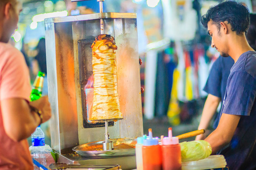Bangkok, Thailand - March 2, 2017: Street vendor is selling grilled kebab, the popular street foods at Khao San Road night market, Bangkok, Thailand. Grilling Kebab Meat Kebabs Khao San Rd Khao San Road KhaoSan Khaosan Rd. Khaosandroad Tourist Tourist Attraction  Tourists Adult Business Day Focus On Foreground Food Food And Drink Freshness Glass Hand Holding Hot Dog Human Hand Incidental People Kebab Kebab Shop Kebabers Khao San Khao San Knok Wua Khao San Rd. Khaosan Road Khaosanroad Lifestyles Meat Men Night Market Night Market In Thailand Night Market, People Preparation  Preparing Food Real People Refreshment Standing Tourist Destination Tray