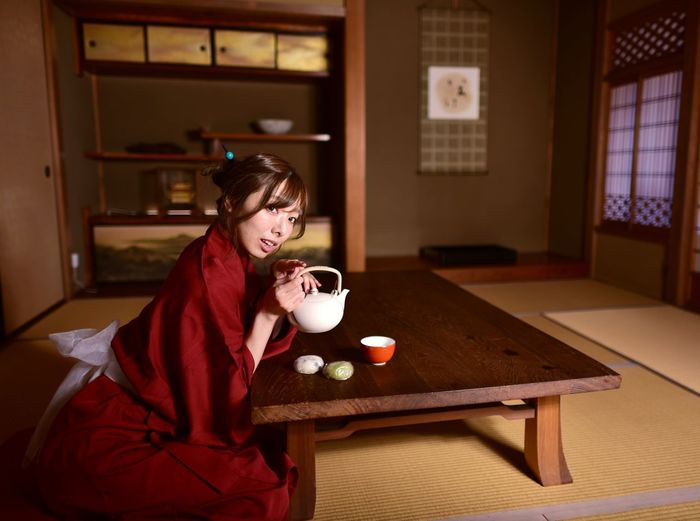Young woman sitting on table at home