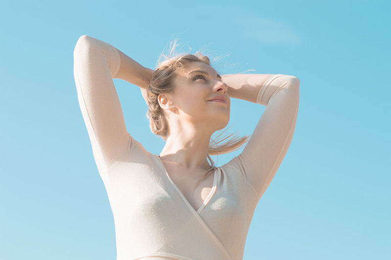 Low angle view of smiling woman with arms raised looking away against blue sky during sunny day