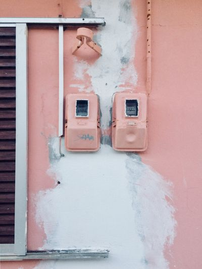 Electricity boxes on old building wall