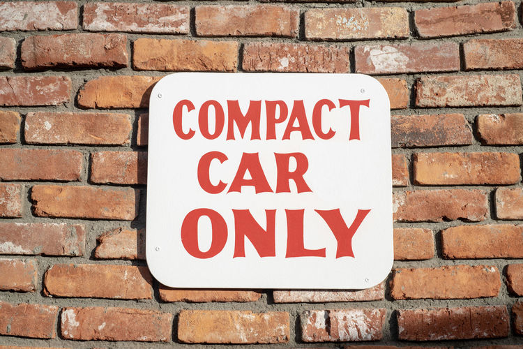Compact Car Only parking sign on brick wall Wall Text Communication Brick Wall Brick Western Script Sign Wall - Building Feature Warning Sign Red No People Close-up Capital Letter Built Structure Architecture Outdoors Information Day Textured  Forbidden Message Parking Sign Compact Car Only