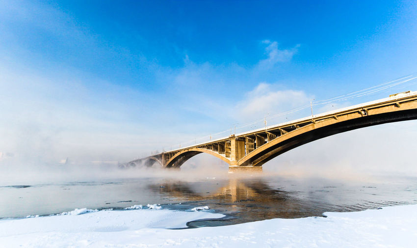 Low angle view of bridge over yenisei river against blue sky on sunny day