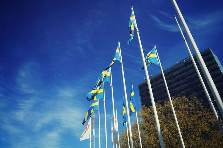 Low angle view of flags against buildings against blue sky