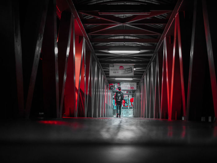 People walking in illuminated corridor of building